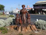 Lakes Entrance / Shops and accommodation along the Esplanade / Wooden sculpture, view west along Esplanade at Bulmer St